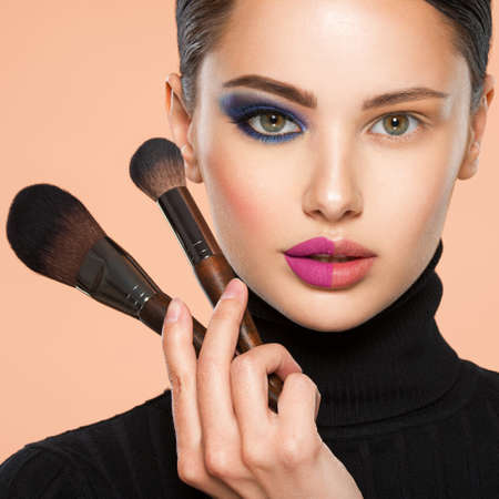 Portrait of a girl with cosmetic brush near face. Woman making makeup on the face using makeup brush. One half face of a beautiful white woman with bright makeup and the other is natural.