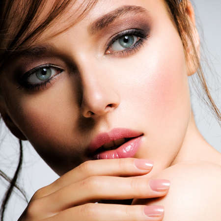 Closeup face of young beautiful woman with a healthy clean skin.  Pretty woman with bright  makeup of eyes. Beautiful white girl. Portrait of a beautiful girl with a long curl of hair hanging down. 版權商用圖片