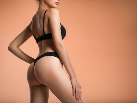 Young  woman with beautiful buttocks. Rear view of a perfect female body. Slim girl in black lingerie posing at the studio. Back view of a female butt.