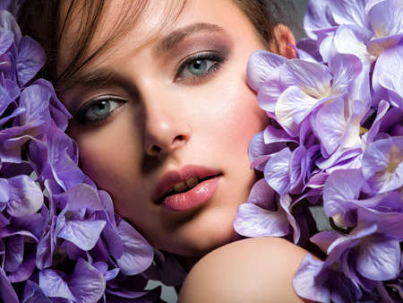 Pretty woman with bright makeup. Beautiful white girl with flowers. Stunning brunette girl with big bouquet  of hydrangeas. Closeup face of young beautiful woman with a healthy clean skin.