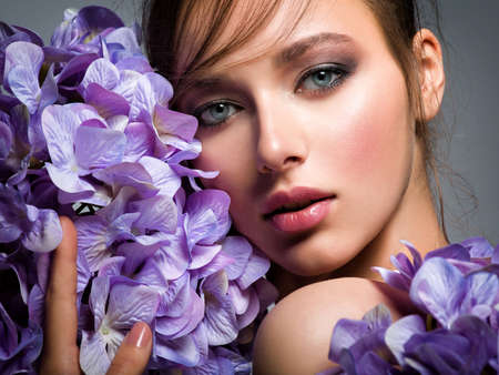 Pretty woman with bright makeup. Beautiful white girl with purple flowers. Stunning brunette girl with big bouquet  of hydrangeas. Closeup face of young beautiful woman with a healthy clean skin.