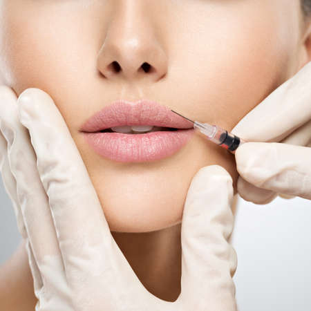 young woman gets botox injection in her lips. Woman in beauty salon. plastic surgery clinic. Banque d'images