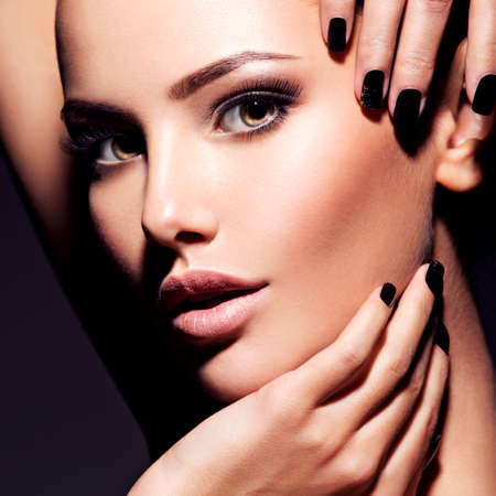 Face of a beautiful girl with fashion makeup and black nails posing at studio over dark background
