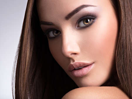 Portrait of a beautiful young woman with long straight hair. Fashion model posing at studio.