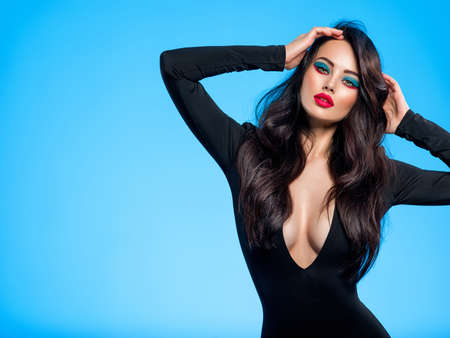 Portrait of beautiful young woman with bright blue makeup.  Pretty girl with long black hair. Brunette woman in a black clothes. Sexy girl. Beautiful brunette with bright red lipstick on her lips. Banque d'images