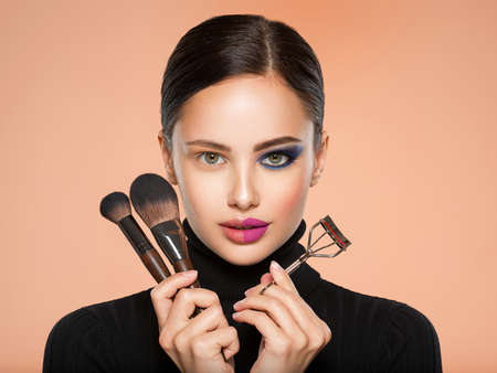 Portrait of a girl with  tools for making makeup near face.  One half face of a beautiful white woman with  bright makeup and the other is natural. Woman holds makeup brush and eyelash curler. Natural and  vivid make-up on a female face.
