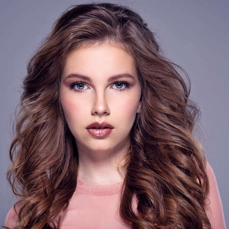 Beautiful brown-hair girl with long, wavy hair. Fashion model posing in the studio on a cool background. Attractive girl with makeup looking at the camera. Pretty caucasian girl with healthy skin.