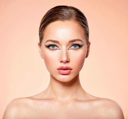 Beautiful girl with makeup in the form of arrows. Face of a young girl close-up with fashionable makeup over beige background. Stylish makeup. Banque d'images