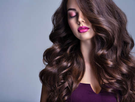 Fashion model with wavy hairstyle. Attractive young  girl with curly hair posing at studio.  Face of a beautiful woman with long brown curly hair. Female face with purple makeup. Violet make-up.