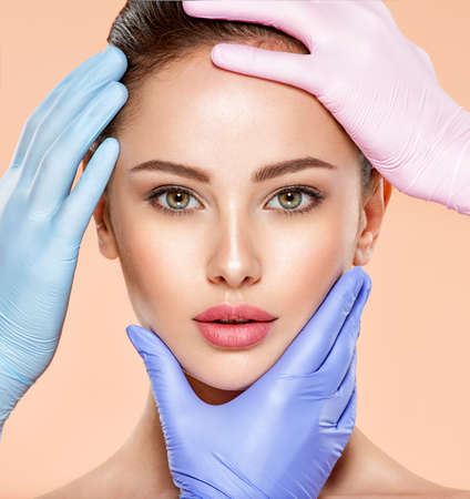 Face skin check before plastic surgery. Beautician touching woman face. Doctor checks a skin before plastic surgery. Beauty treatments. Banque d'images
