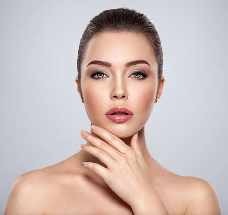 Front portrait of the woman with beauty face - isolated. Beauty face of the young beautiful girl with a healthy skin. Closeup portrait of an attractive female with a beautiful eyes. Skin care concept.