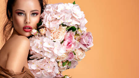 Beautiful white girl with flowers. Stunning brunette girl with big bouquet flowers of roses. Closeup face of young beautiful woman with a healthy clean skin. Pretty woman with bright makeup Banque d'images