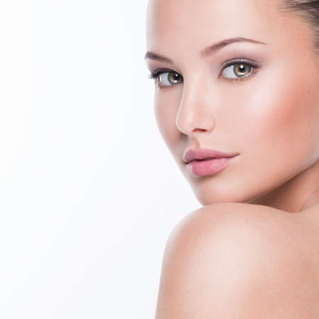 Beautiful face of young caucasian woman with perfect health fresh skin  - isolated on white.  Skin care concept.