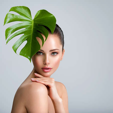 Young beautiful woman with green leave near face and body. Skin care beauty treatments concept.  Closeup girl's face with green leave. White model with clean, health skin of face - posing at studio