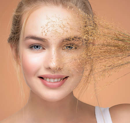 Closeup portrait of young smiling beautiful woman with a healthy  skin of a face. Happy Blonde girl with a bunch spring dry field flowers near the face - over colored background. Beauty face care. 免版税图像