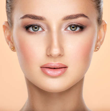 Beautiful face of young caucasian woman with health fresh skin  -  on colored background.  Beauty face concept. Young attractive girl with a healthy skin of  face posing in front of camera.  Natural eye makeup. Banque d'images