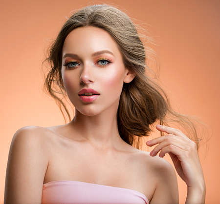 Portrait of a beautiful woman with a long hair. Model with beautiful hair - isolated on beige background. Young girl with hair flying in the wind. Beige eye makeup with a long false black eyelashes.