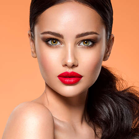 Beautiful white girl with a red lipstick on lips. Stunning brunette girl with long hair tail.  Closeup face of young beautiful woman with a healthy clean skin. Pretty woman with bright makeup Banque d'images
