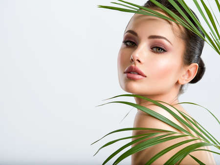 Young beautiful woman with healthy skin of face and palm leaves. Closeup fresh face of an attractive caucasian girl with green plants. Model with bright brown eye makeup. Skin care concept.