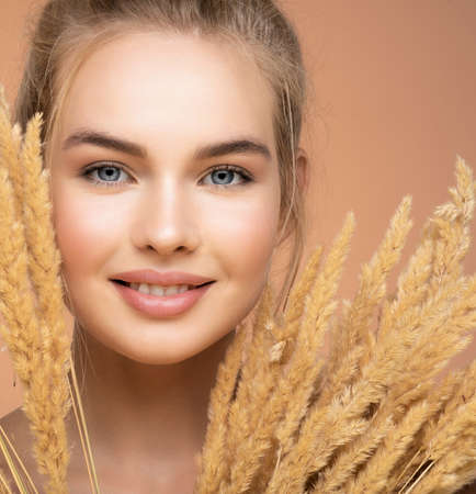Closeup portrait of young smiling beautiful woman with a healthy  skin of a face. Happy Blonde girl with a bunch spring dry field flowers near the face - over colored background. Beauty face care. Banque d'images