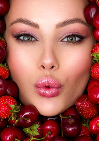 Young girl with bright makeup and a berry background. Beautiful caucasian woman. Attractive woman . Beautiful woman with fashion makeup and a bright vivid background.