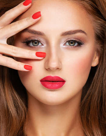 Face of young woman with red nails, lipstick and long brown hair.  Portrait of an attractive model. Girl with bright fashion makeup