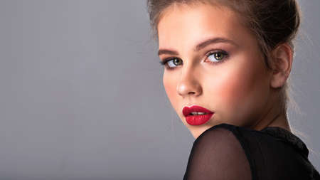 Beautiful girl with brown har. Fashion model with bright makup posing in the studio.  Attractive thin woman looking at the camera. Pretty caucasian girl with red lipstick.