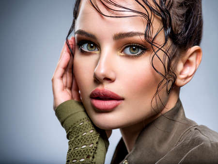 Closeup portrait of a beautiful young fashion woman with brown makeup posing at studio. Beautiful  woman Face with a bang. Model looking at camera.