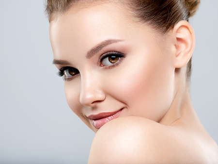 Beautiful face of young smiling woman with clean fresh skin - isolated. Young white happy woman with a clean skin.