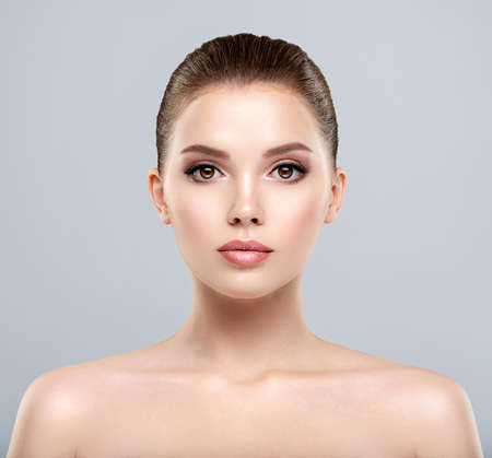 Front portrait of a white young woman with beauty face - isolated. Skin care concept. Young adult caucasian girl with a clean skin. Standard-Bild