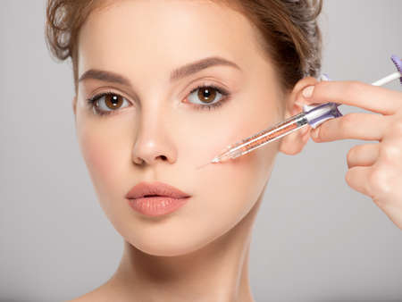 Woman getting cosmetic injection of botox in cheek, closeup. Woman in beauty salon. plastic surgery clinic. Cosmetology procedures concept. Beauty treatment therapy.