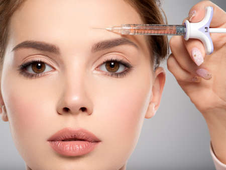 Woman getting cosmetic injection of botox in forehead, closeup. Woman in beauty salon, plastic surgery clinic. Cosmetology procedures concept. Beauty treatment therapy. Stockfoto
