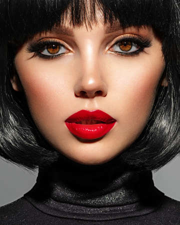Beautiful brunette girl with red lips and black bob hairstyle. Pretty young woman with black hair. Closeup portrait of a model with bright makeup on a face. Fashion portrait of a pretty lady.