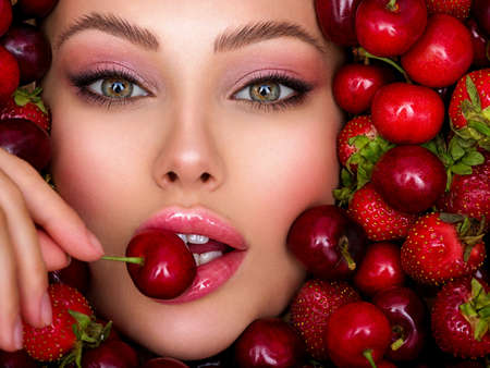 Young girl with bright makeup and a berry background. Beautiful caucasian woman biting a berry. Attractive woman tasting cherry. Beautiful woman with fashion makeup and a vivid background. Stock Photo