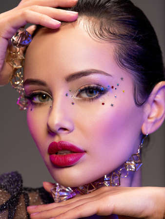 Portrait of beautiful young woman with bright makeup. Shiny sequins on face. Beautiful brunette with fashion jewelry accessories. Face of a girl is highlighted in vivid lights. Girl with earrings.