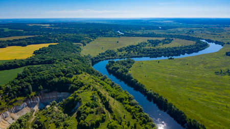 Aerial  view of a beautiful summer  landscape over river. Wide green valley with a river running in the middle. Green meadows. Top view over beauty nature.