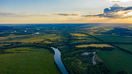 Aerial  view of a beautiful summer hilly  landscape with a  river while sunset. Wide green valley with a river running in the middle. Green meadows. Top view over beauty nature.