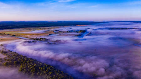 Aerial  view of a beautiful summer  landscape with a fog while dawn.  Photo from drone of a foggy landscape in spring. Top view to land while sunrise. Early morning in nature, misty  weather.