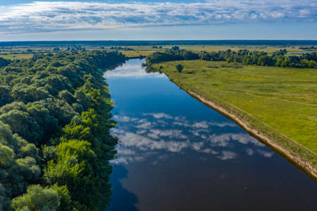 Aerial  view of a beautiful summer  landscape over river while dawn. Top view over river with a smooth water surface reflecting blue sky and clouds. Reklamní fotografie