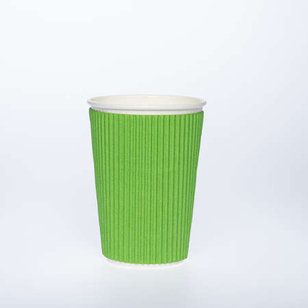 Photo of a disposable green paper cup on a white background. Photo of a colored coffee cup made of recyclable materials. Empty paper coffee cup. Reklamní fotografie