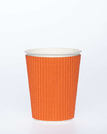 Photo of a disposable orange paper cup on a white background. Photo of a colored coffee cup made of recyclable materials. Empty paper coffee cup. Reklamní fotografie