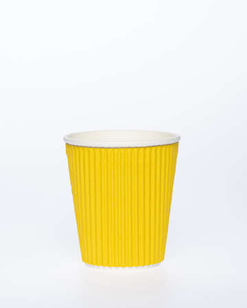 Photo of a disposable yellow  paper cup on a white background. Photo of a coffee cup made of recyclable materials. Empty paper coffee cup.