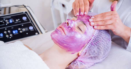 Cosmetologist making  massage the skin of the forehead. Woman in a spa salon on cosmetic procedures for facial care. Beautician applies a woman a therapeutic cream on her face. Reklamní fotografie