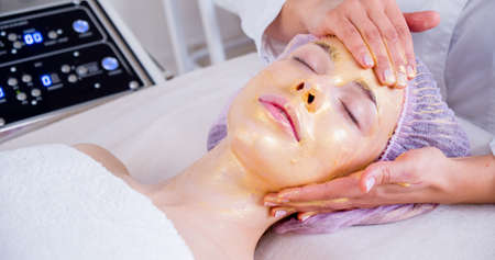 Cosmetologist applies a woman a therapeutic mask on her face. Woman in a spa salon on cosmetic procedures for facial care. Beautician makes a massage of the  face with a moisturizing mask on a face. Reklamní fotografie