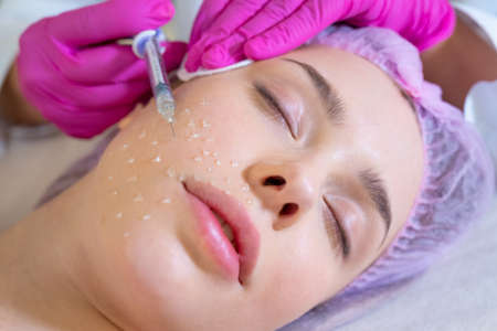 Cosmetologist applying a woman a cosmetic medical gel in a face from a syringe. Woman in a spa salon on cosmetic procedures for facial care.  Beautician makes skin care procedure on a  face. Reklamní fotografie