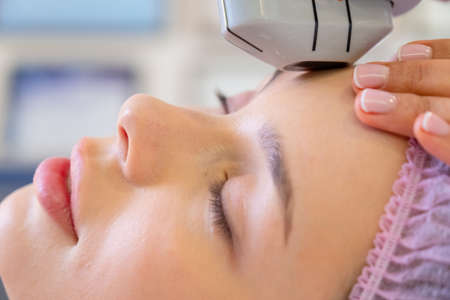 Woman in a spa salon on cosmetic procedures for facial care. Cosmetologist making a woman a therapeutic laser processing on a face. Beautician makes laser procedures on a female face.