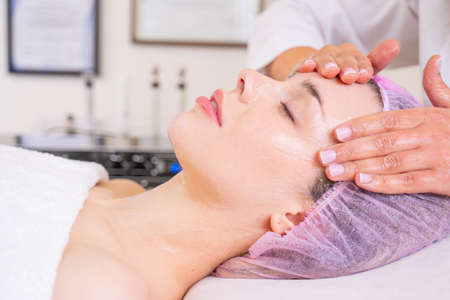 Woman in a spa salon getting face massage for facial care. Beautician makes a massage of the  face with a moisturizing mask on a face.  Beauty treatment concept. Reklamní fotografie