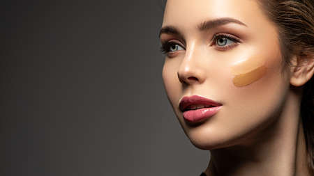 Face close-up with stripes of foundation on the face. The concept of makeup and cosmetics.