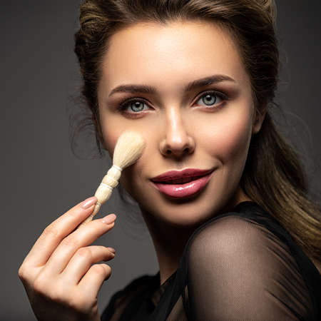 Pretty white model caring of face near cheek. Woman caring of her beauty face with cosmetic tool. Skin care concept. Girl holds item for makeup.