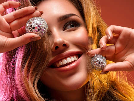 Beautiful Blonde woman  with brightly colored hair  holding shiny glass balls. Glamour concept. Smiling female face. art concept